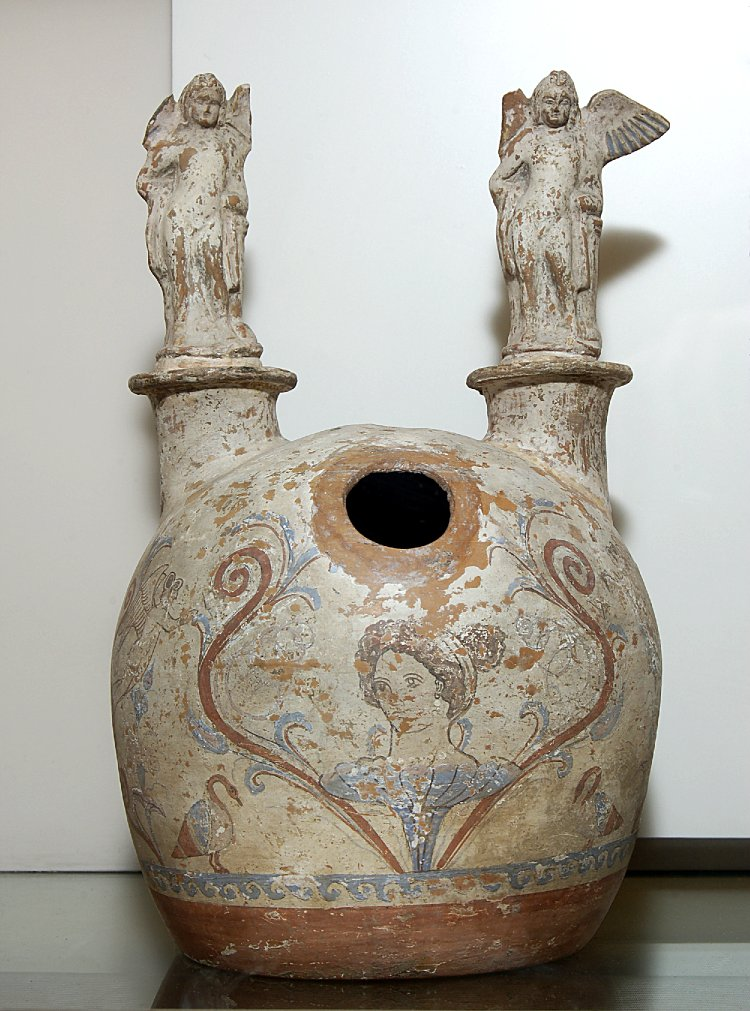 COMPARANDUM: Pottery askos painted with a female head rising up from a flower, with terracotta statuettes of Erotes added above, cr. 310-290BC, Canosa, Apulia, Italy