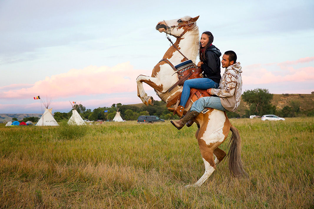Stevana Salazar rides with Arlo Standing Bear, 26 August 2016, photo by Terray Sylvester, Standing Rock camp, Dakota, U.S.A.